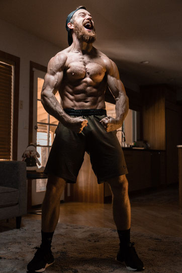 Ein mein durchtrainierter Mann steht in seiner Wohnung. Sein Oberkörper ist frei und er spannt seine Muskeln an.