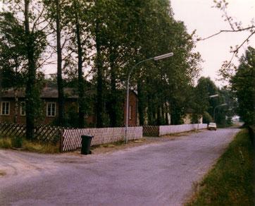 Blick entlang der ehemaligen Lagerstraße. Hinter dem Jägerzaun sind ehemalige Unterkunftsgebäude für Kriegsgefangene zu sehen. Foto: Rose, 1977