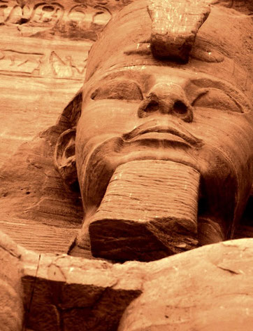 Colossal figures of Ramses II stare down on travelers descending the Nile; Abu Simbel, Egypt.