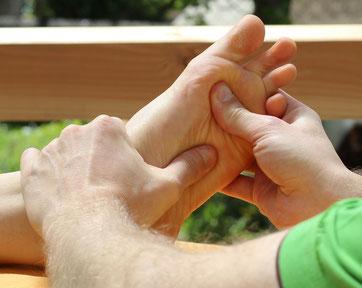 Patrick Schnerr von taloha bodywork in Aalen massiert mit seinen Daumen einen Fuß.