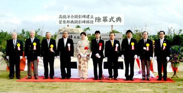 高橋洋介さんの功績を伝えようと建立された顕彰碑と増殖事業記念碑を背に、2人の遺徳をしのぶ関係者=真栄里公園