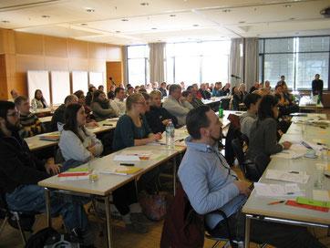 Teilnehmerinnen und Teilnehmer hören aufmerksam zu