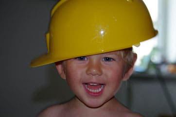 Kind mit Bauhelm  - Blockhaus Bauen - Hausbau - Grundbuch, Kreditinstitut, Förderbank, KfW, Wohneigentum, Baukosten Bauen, Fachwerkhaus, Naturstammhaus, Bausatz, Bausatzhaus -