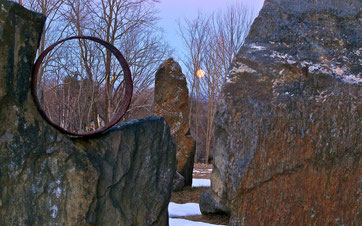 The full 'Worm' moon, setting behind the stone circle at Distant Hill Gardens in Walpole New Hampshire.