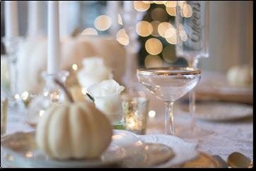 Allestimento Tavolo con piatti di porcellana, bicchieri di cristallo, rose, segnaposto e luci.