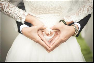 Sposi che mostrano le mani a forma di cuore