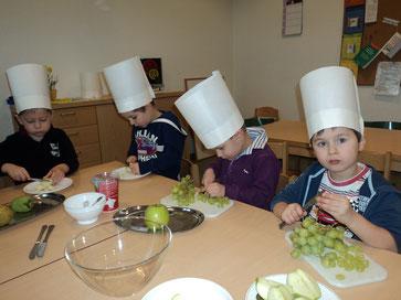Kleine KOCHZWERGE bereiten gemeinsam fleißig einen Obstsalat zu.