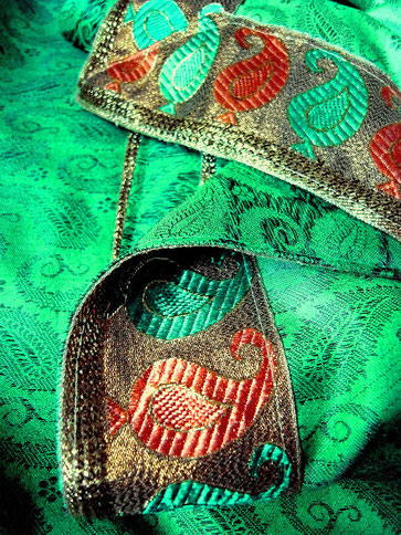 Shiny, apple green, cashmere & cotton, handloom throw with black paisley detail; close-up of bronze, green, peach, paisley, jari border