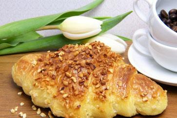 ピンクの花型のお皿に置かれたクッキー。紅茶の入った花柄のカップ&ソーサ。桜の小枝。