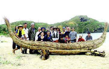 完成した草舟の前で記念撮影する関係者(3万年前の航海徹底再現プロジェクト提供)