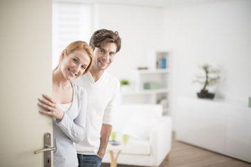 Junges Pärchen heißt Messegäste in Ihrem Apartment willkommen.
