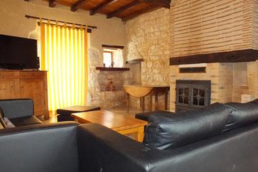 belle pièce à vivre avec télé, cheminé, bureau ,canapé, pierres apparentes...