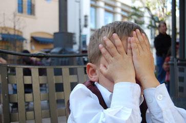Junge, der sich verschämt die Hände vor's Gesicht hält