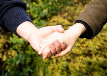 Zwei Menschen reichen einander die Hände