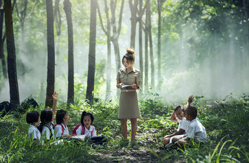 female teacher in front of class in the woods
