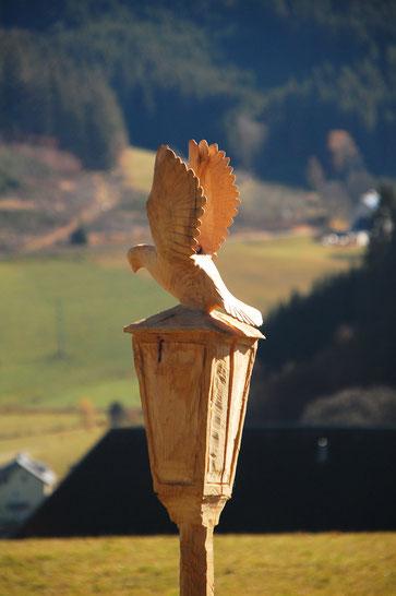 Geschnitzte Laterne aus Lindenholz. Aus der Laterne sitzt eine Taube. Geschnitzt ist da ganze aus einem Stück Holz.