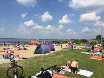 An einem sonnigen Tag tummeln sich viele Menschen am Strand und liegen auf Handtüchern, haben kleine Zelte aufgebaut.