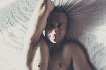 Photo boudoir sexy glamour homme blanc tatoué sur lit Montréal par Marie Deschene photographe