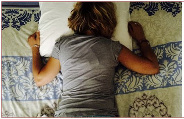 Frau liegt krank auf dem Bett