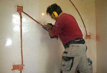Thierry Besançon, électricien à Viriat, entrain d'encastrer de gaines électriques dans les murs pour fixer des prises de courant lors de la rénovation d'une cuisine