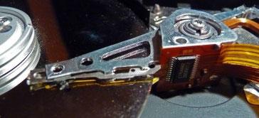 geöffente Festplatte, mit Lesearm, goldener Scheibe und Chip