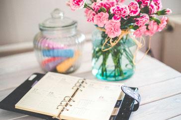 Kalender auf einem weißen Tisch, daneben eine Vase mit rosa Blumen
