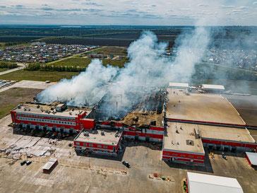Quelle:https://stock.adobe.com/de/images/burning-industrial-distribution-warehouse-aerial-drone-view/292803178?prev_url=detail