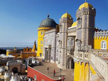 farbenfroher Pena Palast in gelb und rot mit verspielten Türmchen vor blauem Himmel