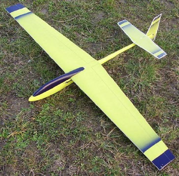 planeur Coquillaj Aeromod jaune et bleu foncé, posé dans l'herbe