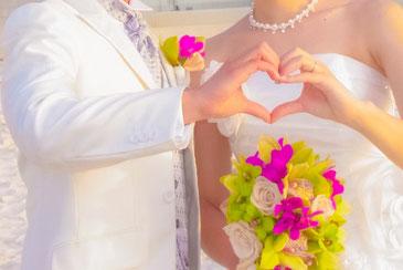ハワイオアフ島でのリゾートウエディング。ビーチでウエディングドレスにブーケを持った花嫁と白いタキシードの花婿がそれぞれの手を合わせハートを型取っている
