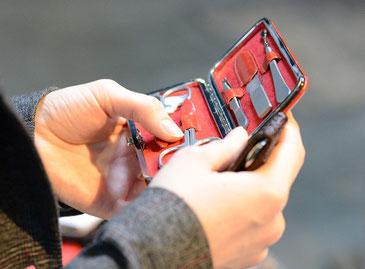 в руках мужчины открытый маникюрный несессер красного цвета