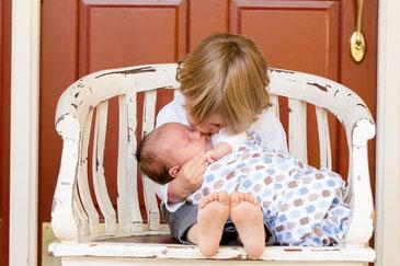 赤ちゃんをケアする子供