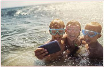 drei lachende Kinder im Wasser mit Handy