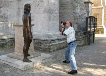 Vor gewaltigen Kirchenmauern sieht man Peter Bach jr. rechts, wie er ein kleinere Bach-Denkmal fotografiert. Bach steht nicht auf einem Sockel sondern neben ihm. Peter Bach hat Jeans und ein kurzes Hemd an.
