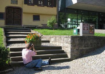 Man sieht Peter Bach jr. von der Rückseite. Er sitzt auf dem Gehweg vor dem Bachhaus und fotografiert über die Eingangsstufen hinweg hinauf zum Gebäude. Rechts sieht man das Bach-Museum. Die Sonne scheint.