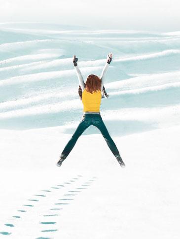 Frau springt im Schnee