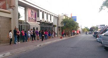 Lange Kolonne vor dem cajero automático (Bankomaten). Chilecito, Dienstag, 19.00 Uhr.