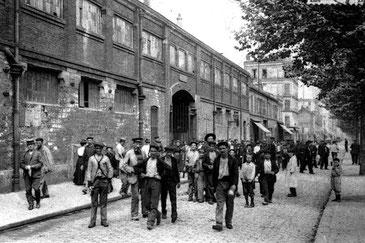 Sur une carte postale d'époque, l'heure de la sortie des ouvriers de la verrerie Legras dans le quartier de la Plaine à Saint-Denis.