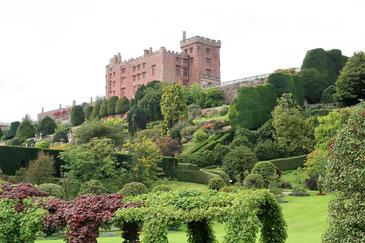 Powis Castle auf einem Hügel mit weitläufigen Gartenanlagen im Vorgergrund