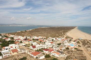 Blick auf die Ria Formosa vom Leuchtturm au, wo man einen Teil des Ortes und den lange Sandstrand mit Dünen sieht