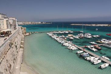 Hafen von Otranto mit türkisfarbenem Wasser und mit einer Reihe kleiner Boote. Auf der linken Seite die Stadtmauer