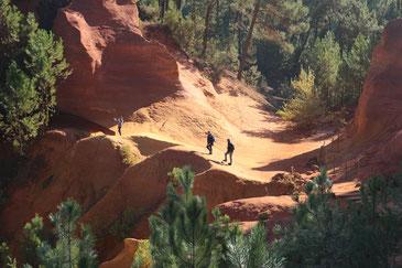 Zwei Personen laufen durch die orangefarbenen Felsen, die von grünen Bäumen umsäumt sind, in den Ockersteinbrüche bei Roussillon