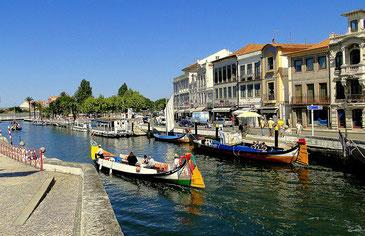 Kanal in Aveiro mit farbenfrohen Holzbooten und bunten Häusern im Hintergrund