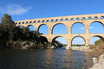 ockerfarbene Doppelbögen der Brücke Pont du Gard von unten aufgenommen, blauber Himmel im Hintergrund