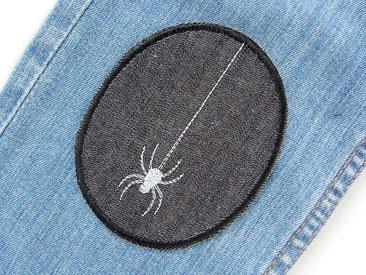 Bild: schwarzer Jeansflicken zum aufbügeln mit gestickter Spinne am Spinnenfaden