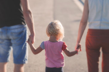 Kind wir zwischen den Eltern an der Hand gehalten
