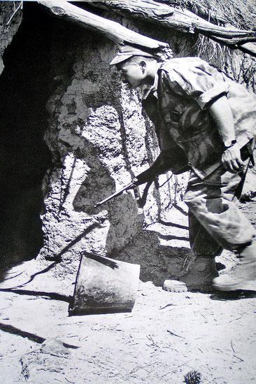 Robert BONAVERO , SGT au 3ème RPIMA, contrôle un gourbi . Il porte tous les attributs des unités para engagées en Algérie : casquette 'Bigeard'', treillis camouflé, pataugas et  carabine US M1...