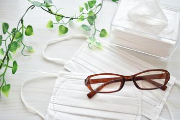 白いデスクに置かれた眼鏡とマスク、ティッシュ