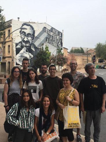 Foto de grup davant del mural de Manuel de Pedrolo