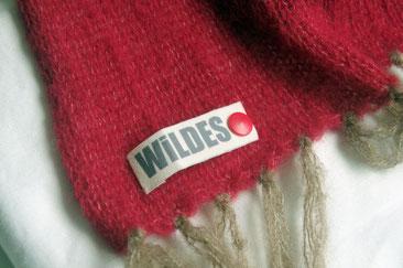 Ecke eines roten Schals mit beigen Fransen, mit rotem Knopf daran befestigt weißes Etikett mit grauer Schrift WiLDES
